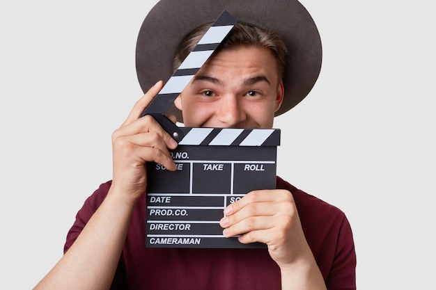 Positive young cameraman holds clapboard near face, has joyful expression, wears hat, prepares for making cutaway, involved in filming, poses on white studio wall. cinematography concept