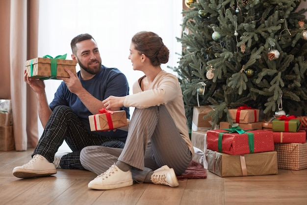 Positive young caucasian couple sitting near christmas tree on floor and unpacking presents together