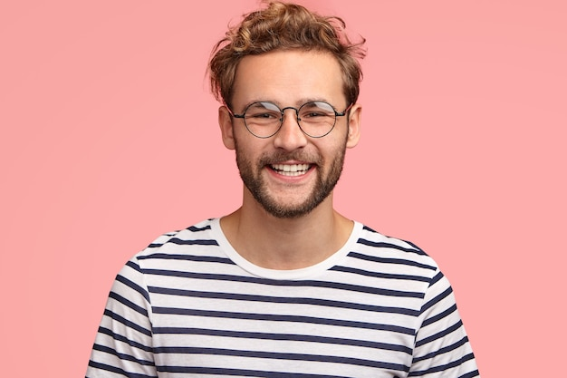 Positive young caucasian male with pleasant friendly smile, shows white teeth, rejoices new stage in life, wears casual striped sweater and round spectacles, stands alone against pink wall.