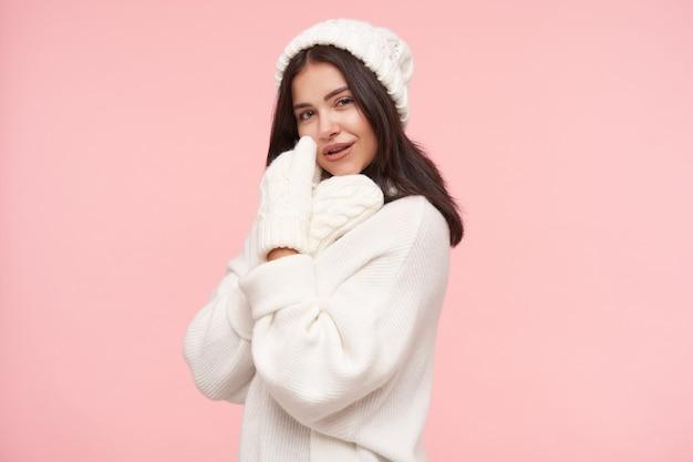 Позитивная молодая очаровательная шатенка с распущенными волосами, касаясь ее лица поднятой рукой и нежно улыбаясь, позирует над розовой стеной в вязаной одежде