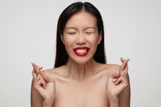 Positive young charming dark haired woman with festive makeup raising hands with crossed fingers and keeping her eyes closed while making wish, posing over white wall