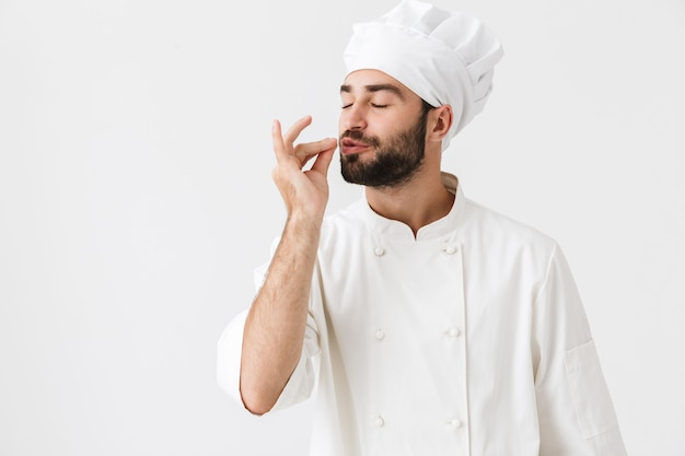 Positive young chef posing in uniform make tasty delicious gesture.