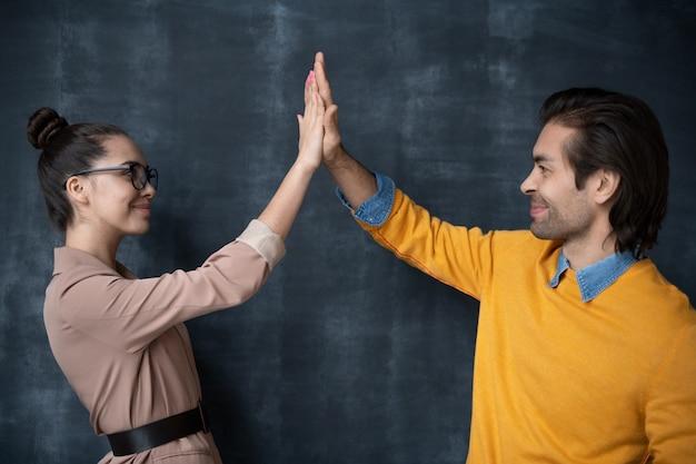 Позитивные молодые коллеги дают друг другу пять на фоне доски
