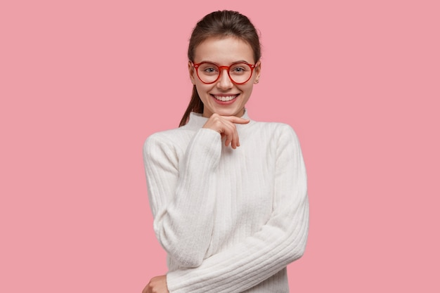 Positive young college student wears white winter sweater, red rim spectacles, keeps hand under chin, smiles broadly