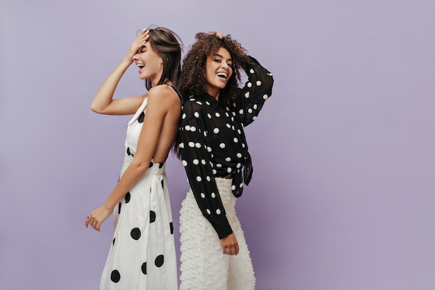 Позитивные молодые крутые девушки с волосами брюнетки в модном модном наряде в горошек смеются на сиреневой изолированной стене