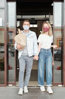 スーパーマーケットを一緒に残しながら紙袋を運ぶカジュアルな服装でポジティブな若いカップル
