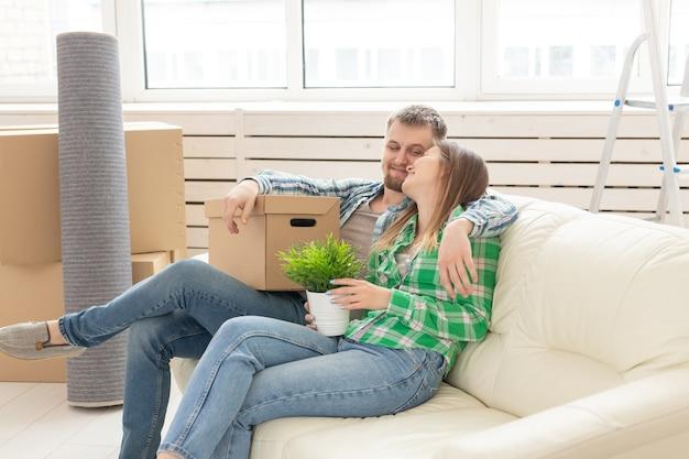 愛の夫と妻のポジティブな若いカップルが新しいリビングルームのソファに座っています