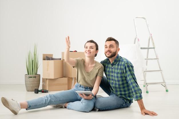 Позитивная молодая пара сидит на полу в новой квартире с движущимися вещами и использует дизайнерское приложение на планшете, обсуждая интерьер