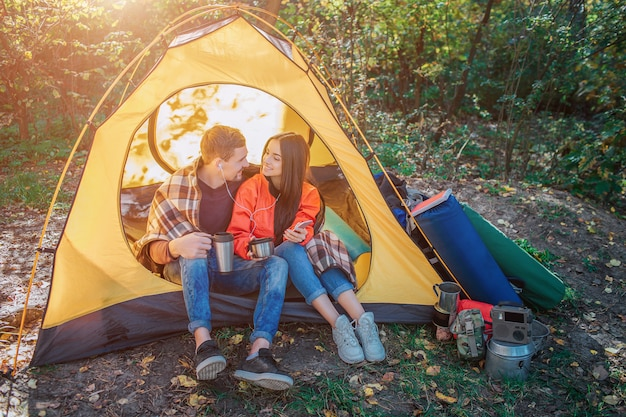 Positive young couple sitting in tent and listen to music through one pair of headphones. they look at each other and smile. she holds phone. he has thermos.