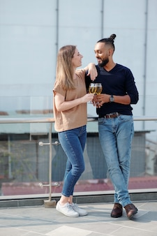 Positive young couple standing on rooftop, drinking champagne and looking at each other