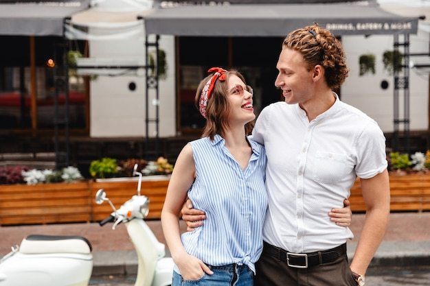 Позитивная молодая пара, стоя вместе с мотоциклом на городской улице