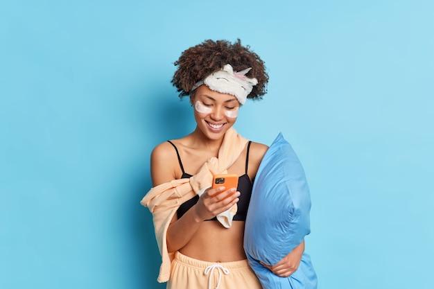 긍정적 인 젊은 곱슬 아프리카 계 미국인은 파자마 수표를 입은 눈 아래에 콜라겐 패치를 적용합니다. 뉴스 피드는 파란색 벽 위에 즐겁게 격리 된 베개 미소를 보유합니다.