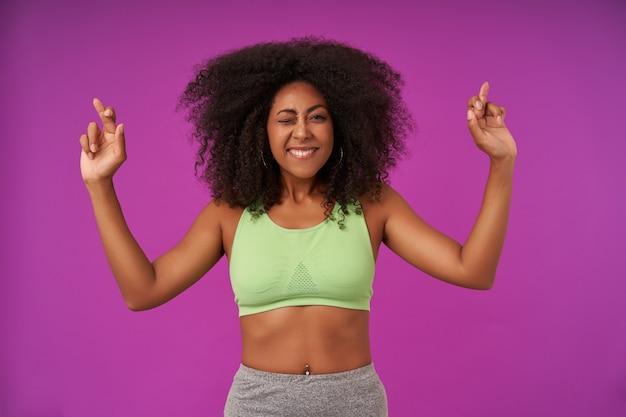 Positiva giovane femmina riccia con pelle scura che indossa abiti sportivi casual, in piedi sul viola con le mani alzate, tenendo le dita incrociate e esprimendo desideri, ammiccando e sorridendo