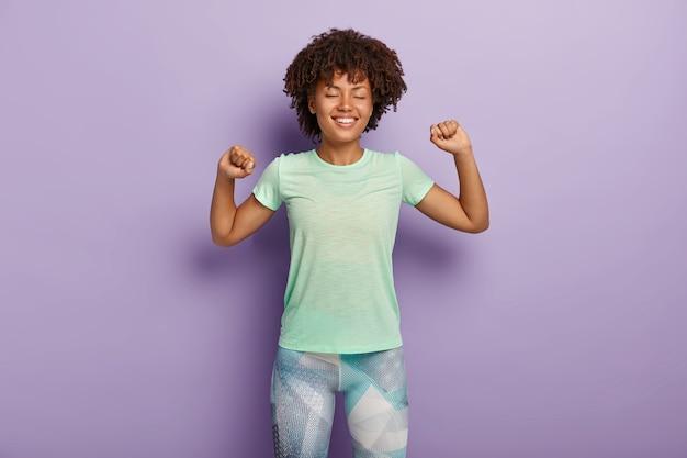 긍정적 인 젊은 곱슬 소녀는 팔을 뻗고, 기뻐하며, 운동을하고, 캐주얼 티셔츠와 레깅스를 입습니다.