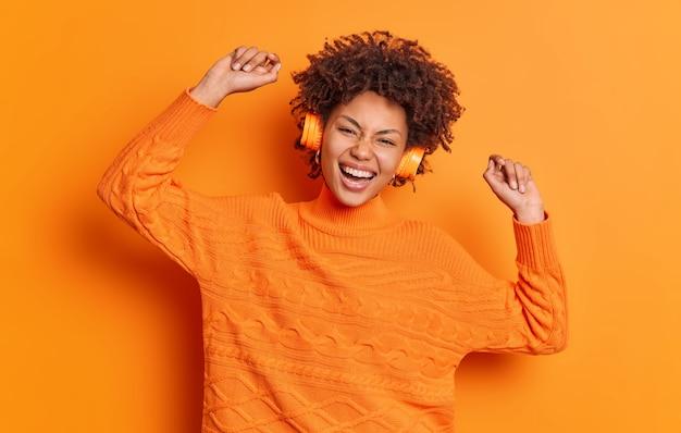 긍정적 인 젊은 곱슬 머리 아프리카 계 미국인 여자는 평온한 춤을 추며 음악의 리듬과 함께 팔을 올리고 움직임은 오렌지 벽 위에 자연스럽게 고립 된 옷을 입고 행복한 감정을 표현합니다.