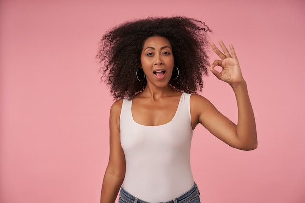 Positive young curly lady with dark skin raising hand with ok gesture cheerfully while standing on pink, wearing white shirt and jeans