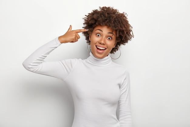 긍정적 인 젊은 곱슬 여자는 성전에 검지 손가락을 쥐고 머리를 기울이고 즐거운 얼굴 표현을 가지고 있으며 둥근 귀걸이와 폴로 넥을 착용합니다.