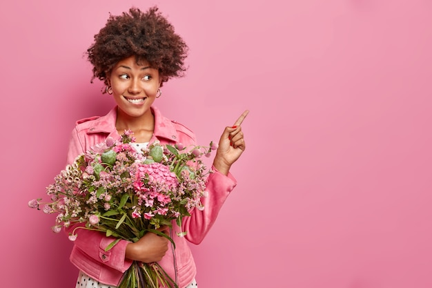 Positive young curly woman poses with nice bouquet of flowers points at blank space shows advertising content wears jacket isolated over pink wall