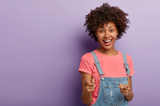 Positive young curly woman selects you, points with both index fingers at camera, smiles happily, wears casual clothes, being glad and satisfied, stands against purple background. you are my type
