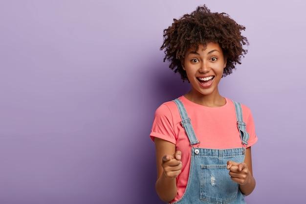 La giovane donna riccia positiva ti seleziona, indica con entrambi gli indici alla macchina fotografica, sorride felice, indossa abiti casual, è felice e soddisfatta, si erge su sfondo viola. tu sei il mio tipo