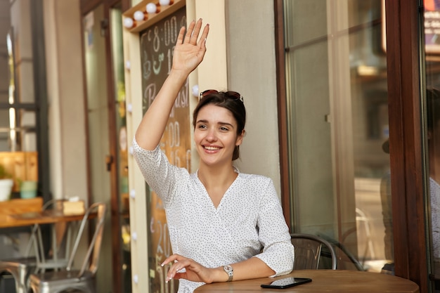 Positive young dark haired female looking aside and smiling happily while raising hand in hello gesture, meeting friends in city cafe on sunny weekend day