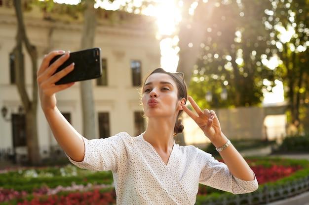 Positiva giovane donna dai capelli scuri con acconciatura casual piegando le labbra in aria bacio e alzando la mano con gesto di vittoria mentre fa foto di se stessa sul suo telefono cellulare