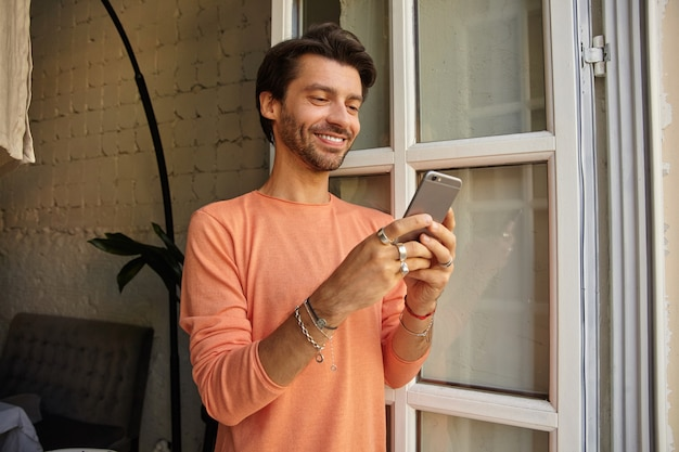 Positive young dark haired male in peach color sweater leaning on opened window, holding mobile phone in hands and looking at screen with wide smile
