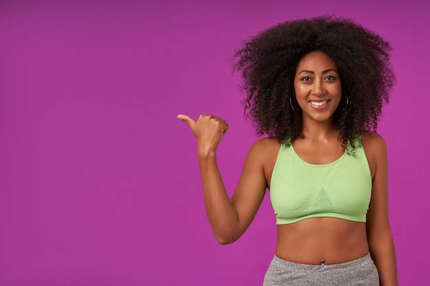 スポーティな服を着て、上げられた手で紫色にポーズをとって、幸せで広い笑顔で親指で脇に見せて、巻き毛のポジティブな若い暗い肌の女性