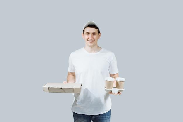 Положительный молодой доставщик еды с коробкой пиццы и кофе.