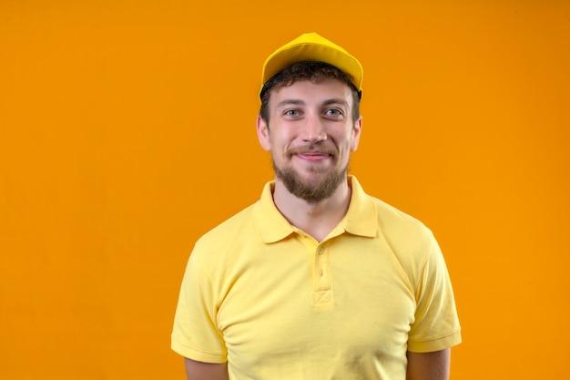 Positivo giovane fattorino in polo gialla e berretto sorridendo allegramente in piedi sull'arancio isolato