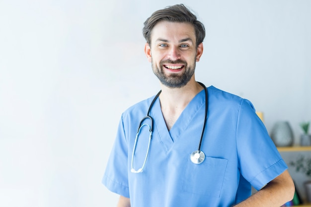 Positive young doctor in scrubs