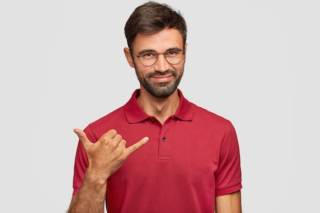 Positive young emotional man posing against the white wall