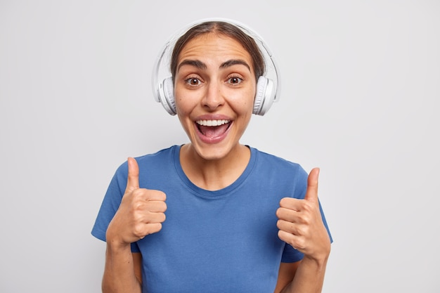 Positive young european woman keeps thumbs up agrees with something shows like sign being in good mood wears casual t shirt listens music in wireless headphones poses against white wall