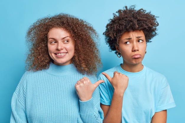 Positive young european woman with curly bushy hair and sad dark skinned female point thumbs at each other suggest to choose stand closely to each other in blue clothes. she is guilty not me