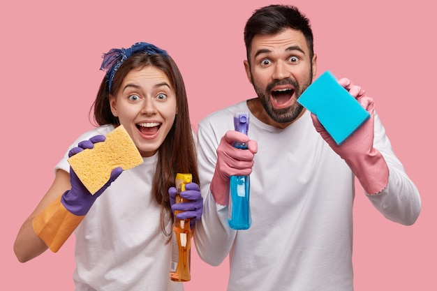 Positive young family couple have positive facial expressions, use chemical washing spray and sponge for cleaning window in room