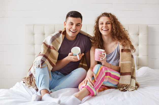 Positive young family couple wear pyjamas, drink coffee in morning at bedroom, enjoy starting new day.
