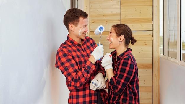 赤い市松模様のシャツを着た女の子と男のポジティブな若い家族は、自宅のライトテラスで修理を楽しんでお互いの鼻をペイントします