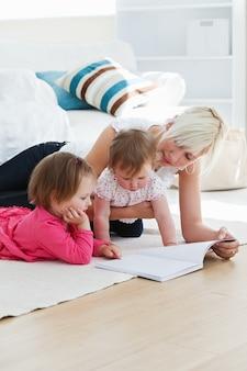 Положительная молодая семья, читающая книгу на полу