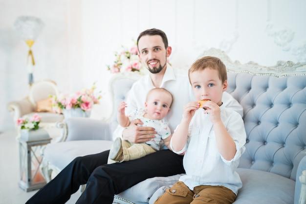 Положительный молодой отец сидит на синем диване