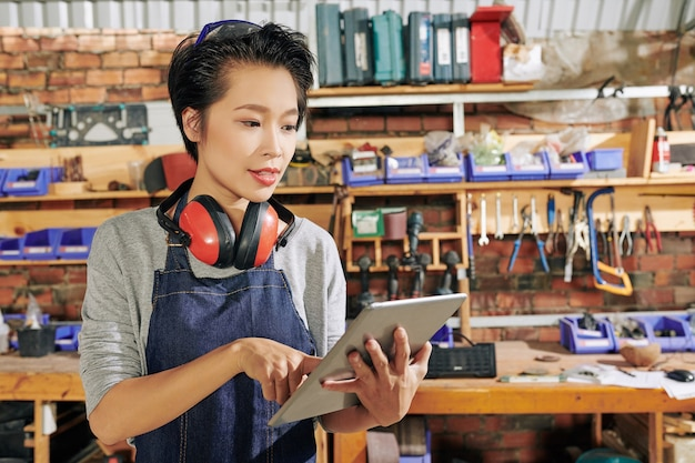 Positive young female carpenter standing in workshop and checking messages from customers on tablet computer