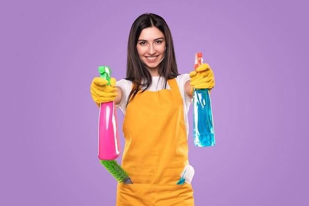 ハウスキーピングサービスを代表しながら、液体洗剤が入ったカラフルなペットボトルを示す黄色いエプロンのポジティブな若い女性クリーナー