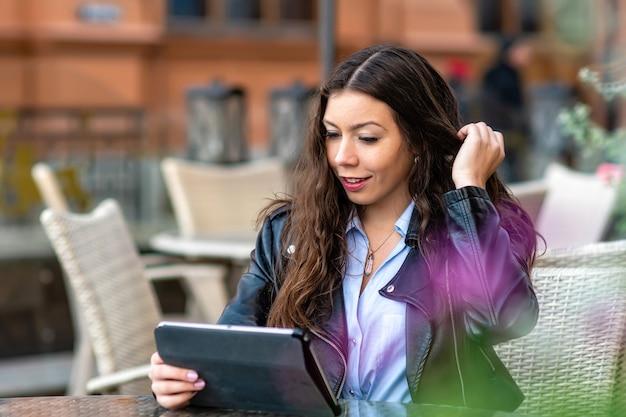 Позитивная молодая женщина в повседневной одежде сидит в уличном кафе во время работы над удаленным проектом на цифровом планшете
