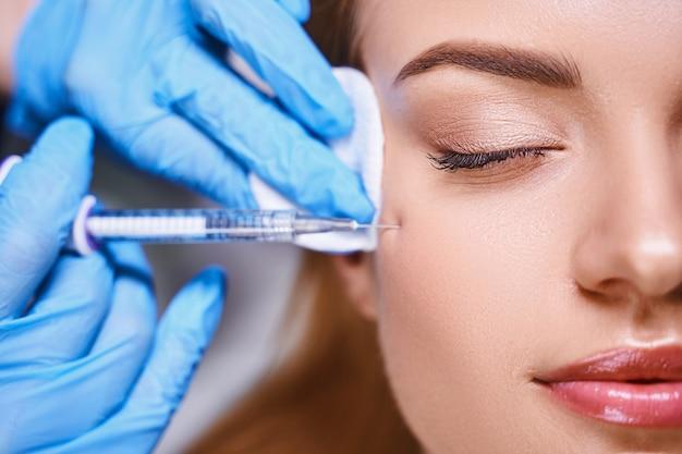 긍정적인 젊은 여성이 미용실에서 보톡스 주사를 맞아 얼굴 주름을 예방하고 있다