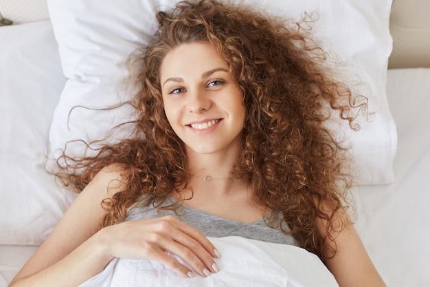暖かい毛布の下の快適なベッドで肯定的な若い女性モデルは寝室にあるように幸せな表情を持っています。リラクゼーションと就寝時間のコンセプト