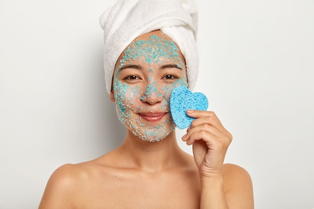 Positive young female model with pleasant smile, applies natural scrub on face, stands with naked body, keeps blue sponge near face, looks happily