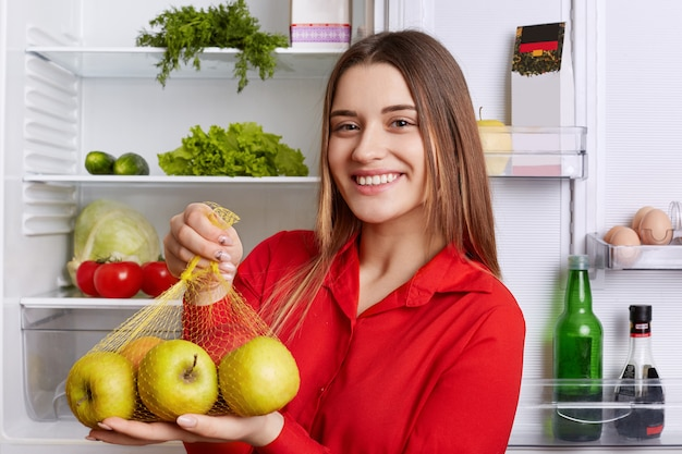 Positive young female with glad expression comes from grocer`s shop with new purchase, shows fresh apples, going to put them in fridge