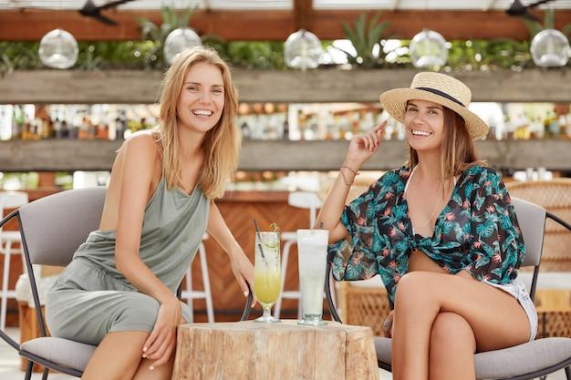 긍정적 인 젊은 여성은 야외 카페테리아 나 바에 앉아 신선한 여름 칵테일을 마시 며 즐거운 대화를 나누고 재현하며 긍정적 인 표현을합니다. 레즈비언은 관계를 즐기고 데이트 또는 파티를