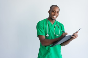 Positive young general practitioner filling in medical record.