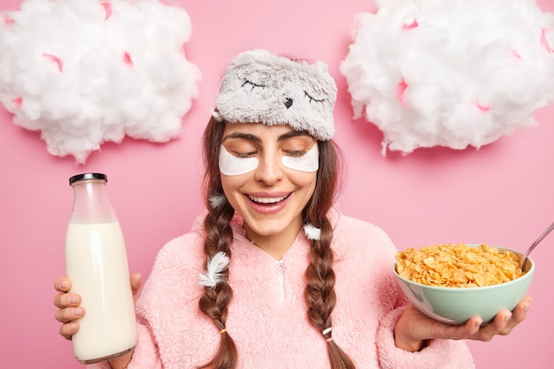 Positive young girl has two pigtails wears blindfold and pajama