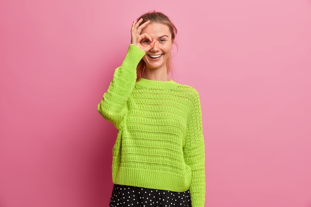 Positive young girl makes okay gesture over eye, smiles happily, has fun, recommends product, wears knitted sweater, assures everything is good, says no problem rates excellent choice